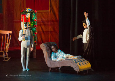Nutcracker Prince waits while Drosselmeyer wakes Marie